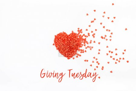 Photo for Giving Tuesday is a global day of charitable giving after Black Friday shopping day. Charity, give help, donations and support concept with text message and red heart shaped confetti white background - Royalty Free Image