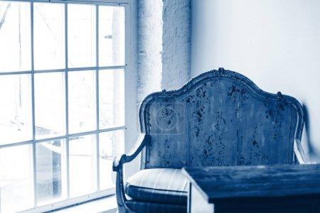 Photo pour Fauteuil vintage et une table en bois dans une pièce avec grande fenêtre et lumière naturelle du soleil. Couleur de l'année 2020 classique bleu tonique - image libre de droit