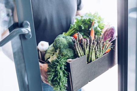 Photo for Fresh organic greens and vegetables delivery. Man hands holding box with farmer bio crop delivering in the house doorway. Small local business support. Online grocery shopping - Royalty Free Image