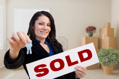 Hispanic Female Real Estate Agent with Sold Sign and Keys in Roo