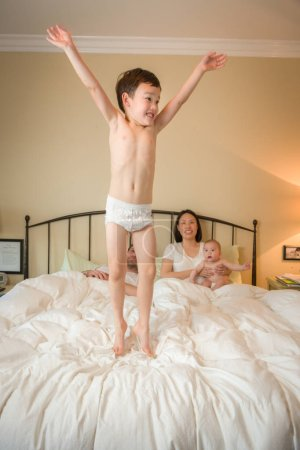 Mixed Race Chinese and Caucasian Boy Jumping In Bed with His Fam