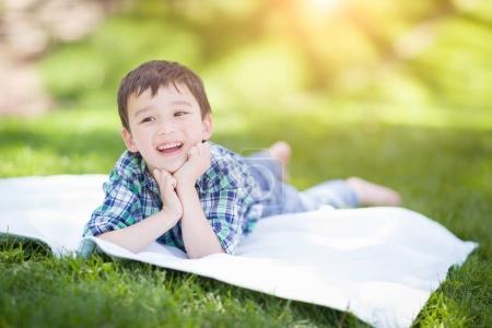 Photo pour Race mixte chinois et caucasien jeune garçon se détendre à l'extérieur sur l'herbe - image libre de droit