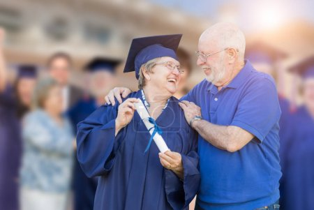 Photo for Senior Adult Woman In Cap and Gown Being Congratulated By Husband At Outdoor Graduation Ceremony. - Royalty Free Image