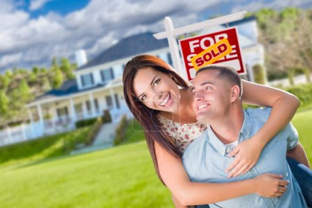 Playful Excited Military Couple In Front of Home with Sold Real Estate Sign.
