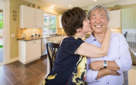 Photo for Happy Senior Chinese Couple Kissing Inside Beautiful Custom Kitchen. - Royalty Free Image