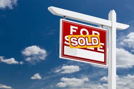 Left Facing Sold For Sale Real Estate Sign Over Blue Sky and Clouds With Room For Your Text.