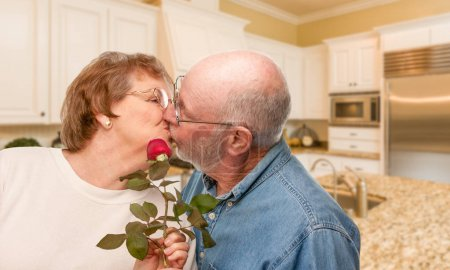 Happy Senior Adult Man Giving Red Rose to His Wife Inside Kitchen