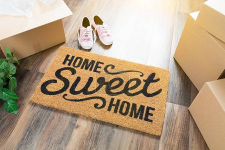 Photo for Home Sweet Home Welcome Mat, Moving Boxes, Pink Shoes and Plant on Hard Wood Floors. - Royalty Free Image