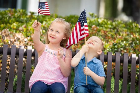Young Sister and Brother Comparing Each Others American Flag Size On The Bench At The Park.
