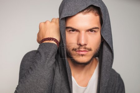 casual man with hoodie on holds hand near head