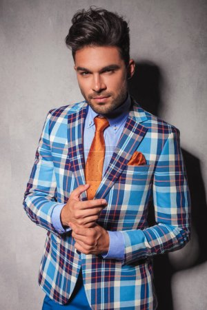 young sexy man in checkered suit stainding with palms together