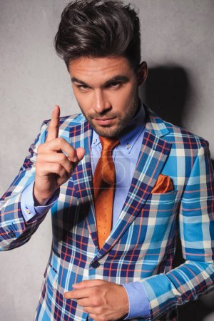 elegant man in checkered suit gesturing for you to behave