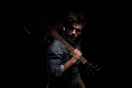 Photo for Dramatic young guitarist looking back while holding guitar on shoulder, on black studio background - Royalty Free Image