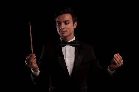 elegant man in tuxedo conducting an orchestra