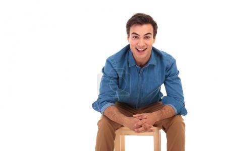 Photo for Smiling casual man resting elbows on knees while sitting on chair on white background - Royalty Free Image