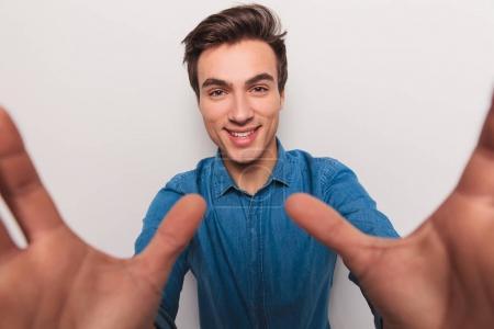 Photo pour Heureux jeune homme tenant la caméra et sourit, photo de studio - image libre de droit
