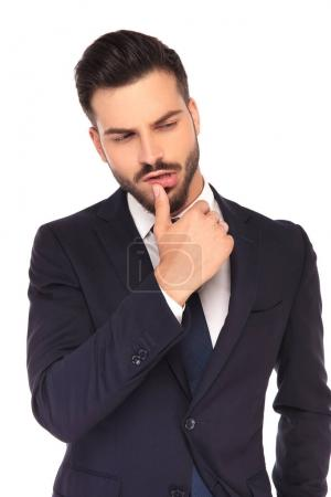handsome young business man touching lips with his thumb