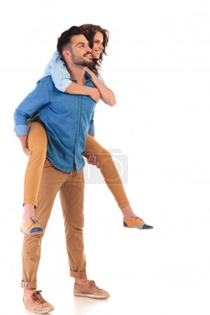 side view  of  smiling man carrying his girlfriend on back