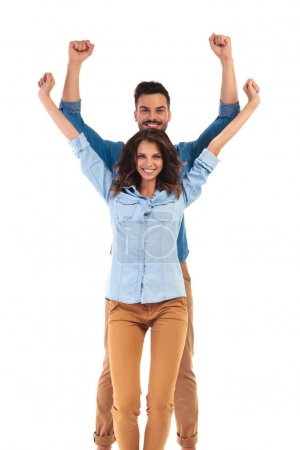 casual couple celebrating success with hands in the air