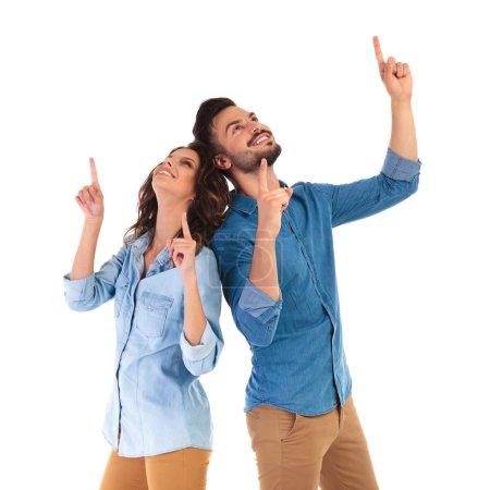 Photo pour Heureux couple occasionnel pointant vers le haut sur quelque chose sur fond blanc - image libre de droit
