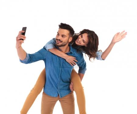 woman on the back of man  while he takes  selfie