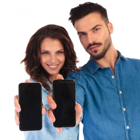 smiling casual couple showing the blank screens of their phones
