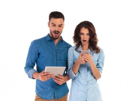 amazed casual couple reading surprising things on their mobile d