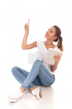 happy casual woman holding tablet and points up