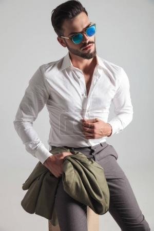 young man in sunglasses fixing shirt while sitting