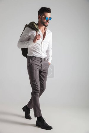 serious man with coat on shoulder stepping forward