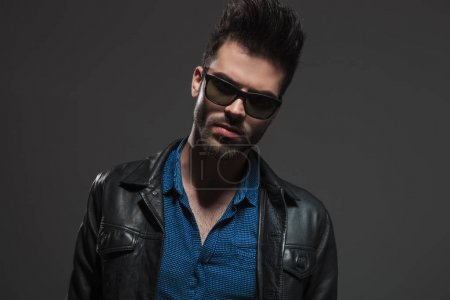 hot man in leather jacket and sunglasses poses