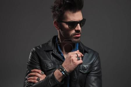 hot man in leather jacket and sunglasses looking to side
