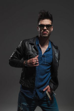 fashion man standing with hand in pocket and holds collar