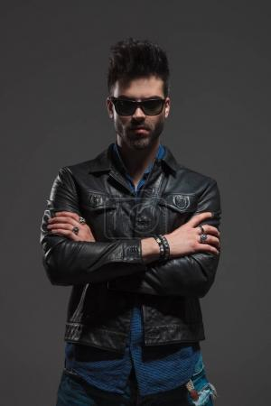 fashion man in leather jacket  standing with hands crossed