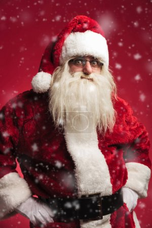Photo for Amazed santa claus standing with hands on waist while snowing on red background - Royalty Free Image