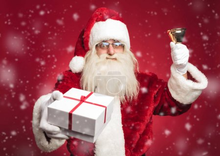 Photo for Happy santa claus ringing his bell and offering a present to everybody while snowing on red background - Royalty Free Image