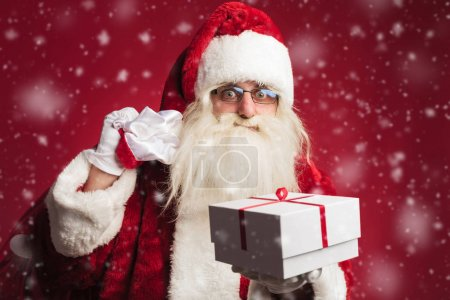 Photo for Santa claus holding bag on shoulder and offering a gift box on red background with snow flakes - Royalty Free Image