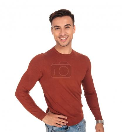 happy young fit man with hand on waist