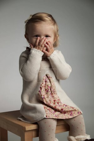 excited little girl covering her mouth with palms