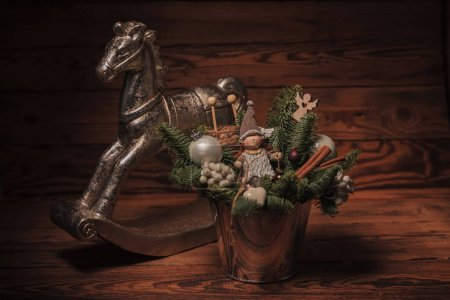 bucket with christmas decorations near toy horse