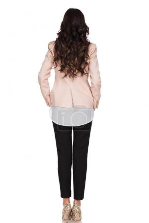 back view of a businesswoman standing with hands in pockets