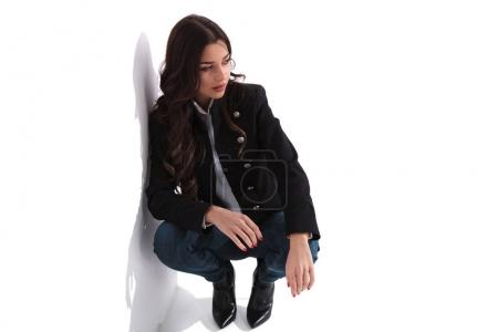 attractive young woman standing down against white wall