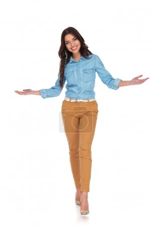 Photo for Happy young casual woman walking and welcoming on white background - Royalty Free Image