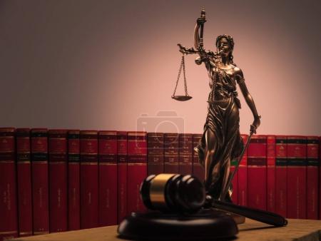 Photo pour Statue de justice, livres de droit et marteau en bois tourné en studio - image libre de droit