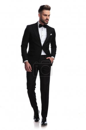 Photo for Serious handsome man in tuxedo walks and looks to side on white background - Royalty Free Image