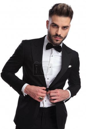 portrait of a sexy man buttoning his tuxedo