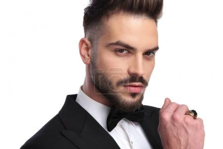 handsome man in tuxedo and bowtie wearing big ring