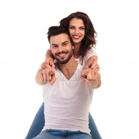 Foto de Feliz joven pareja señalando dedos juntos sobre fondo blanco - Imagen libre de derechos