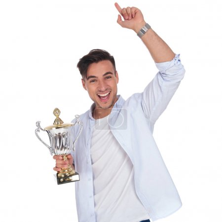 excited young casual man holding trophy cup is celebrating