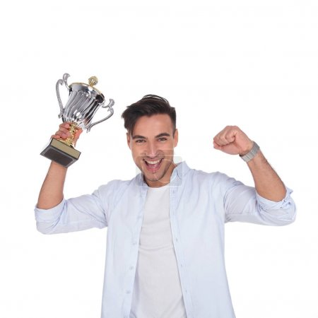 excited young casual man with trophy cup award is celebrating